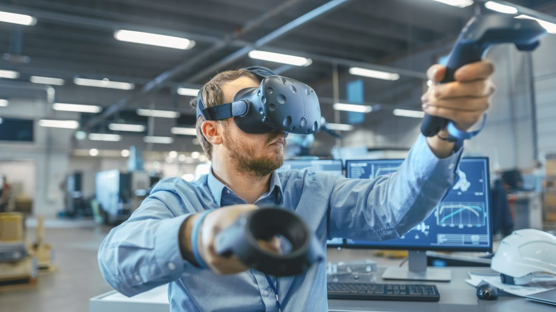 Portrait Shot of the Industrial Engineer Wearing Virtual Reality Headset and Using Controllers, ready to Work. In the Background Manufacturing Plant and Monitors.